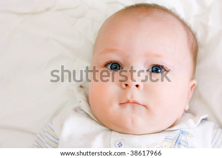 portrait of very serious baby on white bedsheet