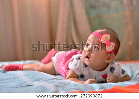 Portrait of very sweet little baby girl lying in the bed - stock photo