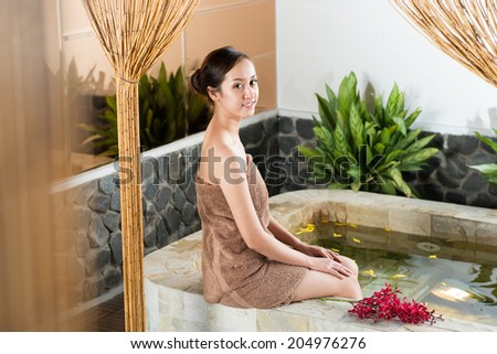 Portrait of Vietnamese woman relaxing in spa salon - stock photo
