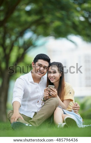 Portrait of Vietnamese young couple with smartphone resting in park