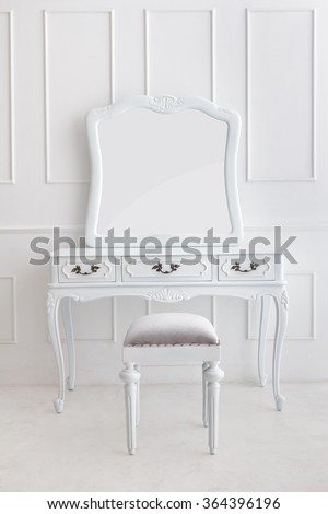 portrait of vintage vanity table set with stool and mirror on white patterned wall - stock photo