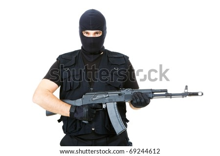 Portrait of violent killer holding firearm and looking at camera with balaclava on his head - stock photo
