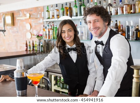 Portrait of waiter and waitress smiling in restaurant