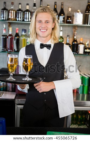 Portrait of waiter holding tray with glasses of beer in restaurant