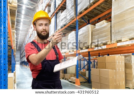 Portrait of Warehouse worker in a yellow helmet in logistic center - stock photo