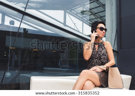 Portrait of wealthy businesswoman in sunglasses using smart phone while looking aside, beautiful female employed speaking on the phone while sitting alone near modern glassy building - stock photo