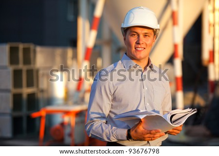 portrait of well-dressed man full of belief in the eyes standing against the construction in hard hat - stock photo