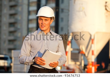 portrait of well-dressed man in hard hat standing against the construction - stock photo
