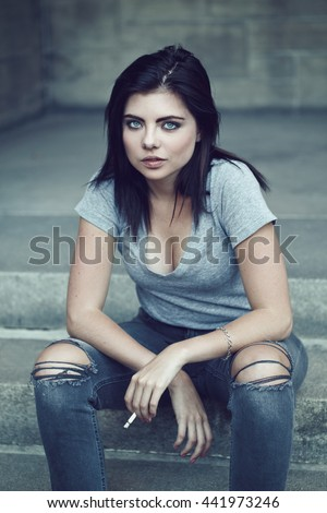Portrait of white Caucasian beautiful young sexy brunette woman with light blue green eyes in ripped jeans, t-shirt holding smoking cigarette looking in camera, toned with filters, lifestyle concept - stock photo