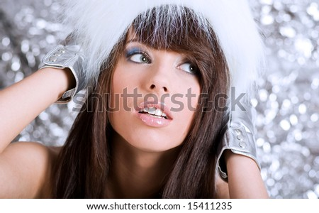 Portrait of winter girl wearing white fur. silver background