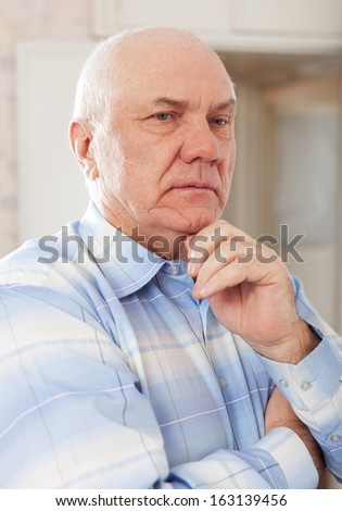 portrait of wistful grizzled man in interior