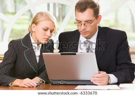 Portrait of woman and man looking at the monitor of laptop together