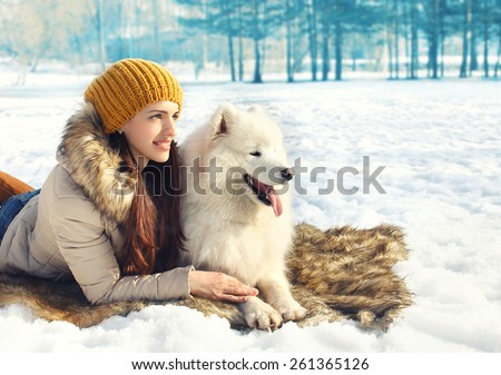 Portrait of woman and white Samoyed dog lying on the snow in winter day - stock photo
