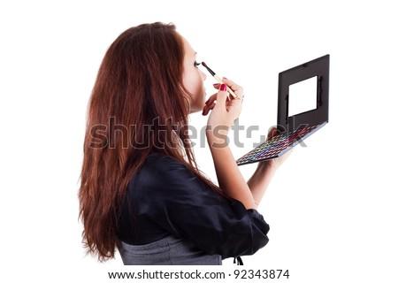 Portrait of woman applying eyeshadow isolated on white - stock photo