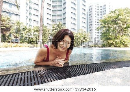 Portrait of woman bathing in the pool - stock photo