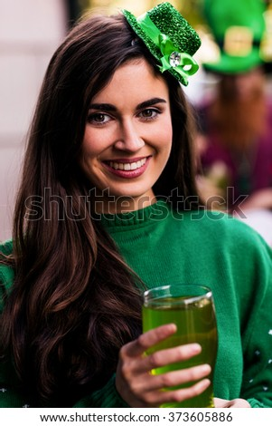 Portrait of woman celebrating St Patricks day with a green pint - stock photo