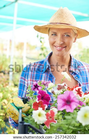 Portrait of woman cultivating flowers - stock photo