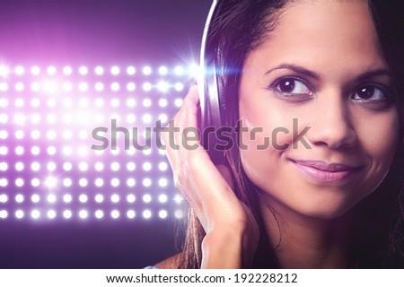 Portrait of woman dj enjoying music on headphones and nightclub lights - stock photo