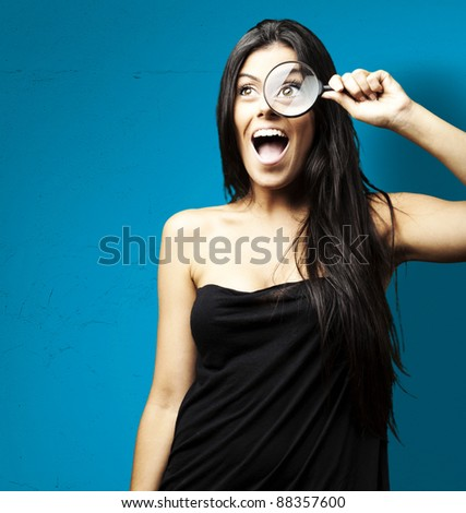 portrait of woman excited looking through a magnifying glass over blue background - stock photo