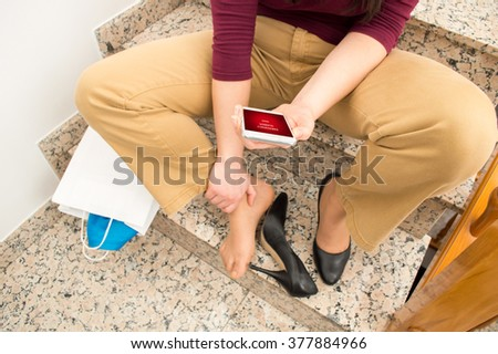 portrait of woman falling on the stairs and calling by phone to emergency  - stock photo
