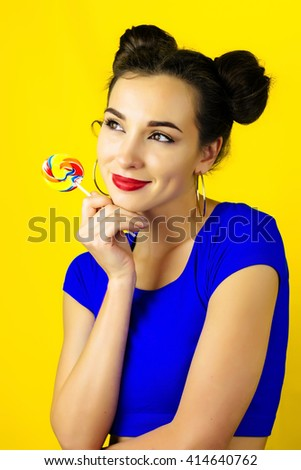 Portrait of woman, girl lick colorful round candy on the stick with beautiful make-up on yellow background with mouse or cat head ears. Colorful fashion portrait of joyful playful woman with lollipop. - stock photo