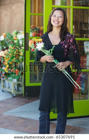 Portrait of woman holding flowers - stock photo