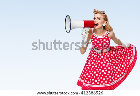 Portrait of woman holding megaphone, dressed in pin-up style red dress in polka dot and white gloves, on blue background, with blank copyspace area for text or slogan