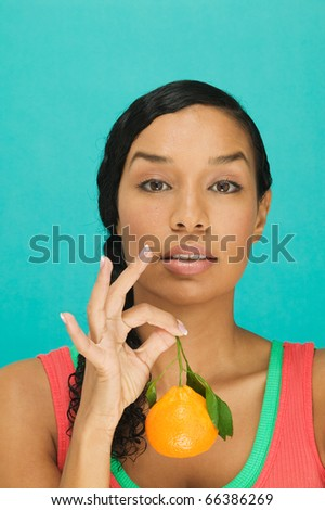 Portrait of woman holding tangerine