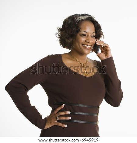 Portrait of woman holding telephone to ear and smiling.