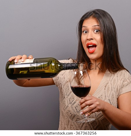 Portrait of woman holding wine bottle and glass against gray background - stock photo