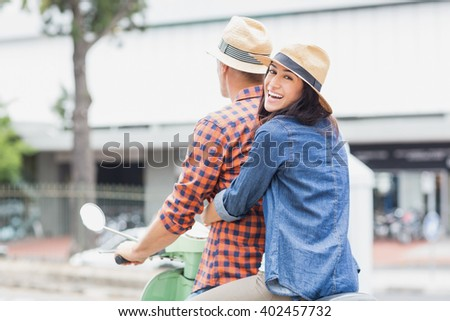 Portrait of woman hugging man from behind on moped in city - stock photo