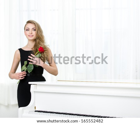 Portrait of woman in black dress handing red rose and standing near the piano. Concept of music and art - stock photo