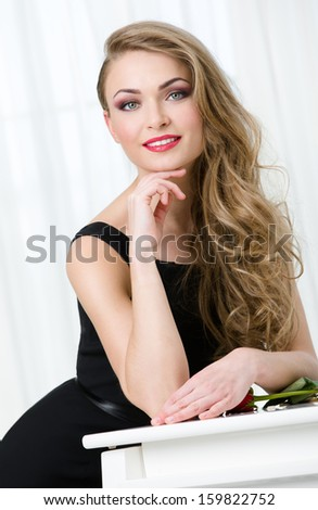 Portrait of woman in black dress leaning at the piano. Concept of music and art - stock photo