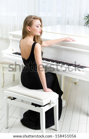 Portrait of woman in black dress sitting and playing piano. Concept of music and arts - stock photo