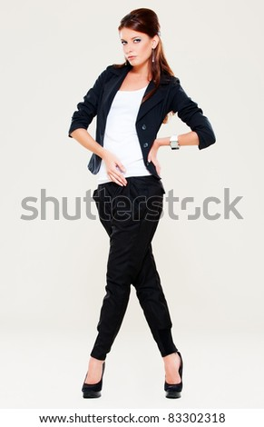 portrait of woman in black suit over grey background - stock photo