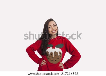 Portrait of woman in Christmas sweater standing with hands on hips over gray background - stock photo