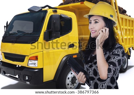 Portrait of woman in hard hat talking by mobile phone while holding a digital tablet near the big truck - stock photo