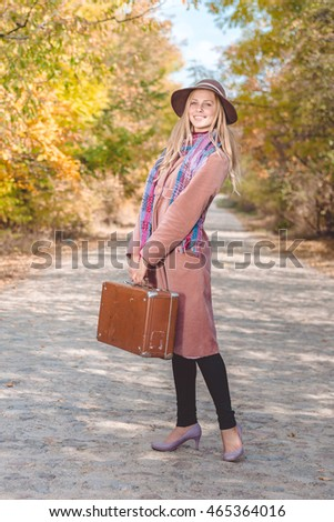 Portrait of woman in hat and coat with suitcase on the road outdoors background