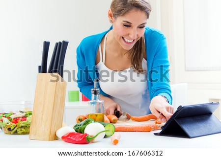 Portrait of Woman in kitchen looking for a recipe on the Internet - stock photo