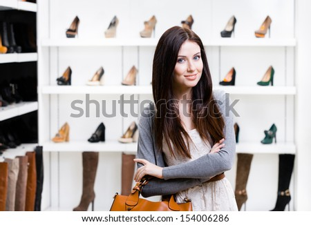 Portrait of woman in shopping center in the section of female pumps. Concept of consumerism and stylish purchase - stock photo