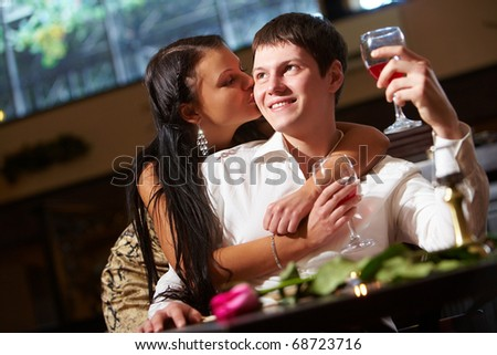 Portrait of woman kissing her boyfriend in the restaurant - stock photo