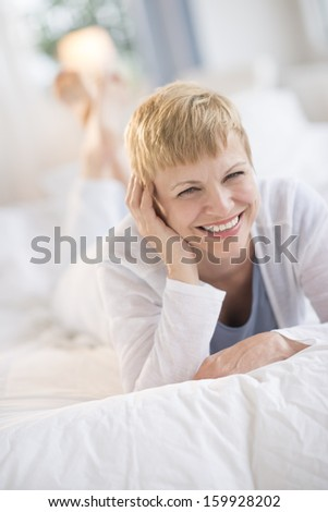 Portrait of woman lying in bed at home