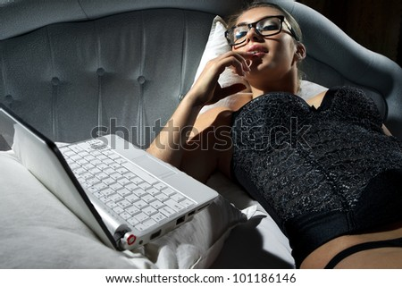 Portrait of woman lying on bed with a laptop and play with herself - stock photo