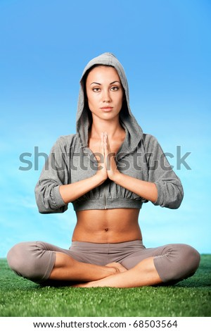 Portrait of woman meditating in pose of lotus and holding hands together - stock photo