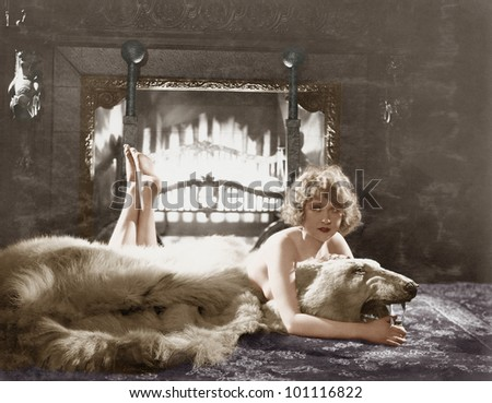 Portrait of woman on bear rug with fireplace - stock photo