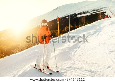 Portrait of woman on skis during winter season. Girl skiing in a mountain resort on the slopes - stock photo