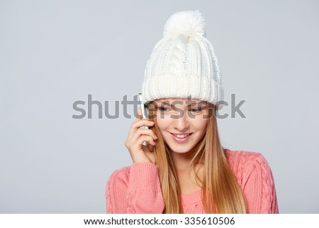 Portrait of woman on white background wearing woolen hat and sweater talking on cell phone - stock photo