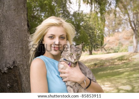 Portrait of woman or girl with pet cat in garden - stock photo