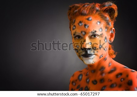 Portrait of woman painted as leopard - stock photo
