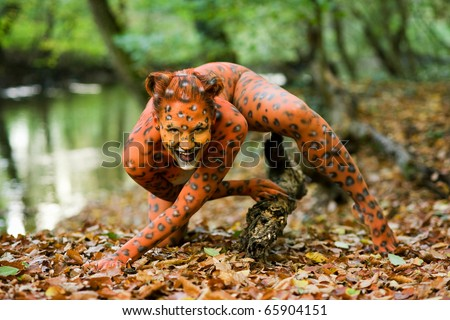 Portrait of woman pointed as leopard in a forest - stock photo